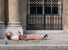 Relax (graveur8x) Tags: girl lying blond summer paris france street streetphotography reading book europe light sun sunglasses glasses fence woman sneakers young lumix lumixgx80 panasonic panasonicdmcgx80 olympus olympusm45mmf18 microfourthirds m43 outdoor water bottle stairs