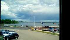 Window view of storm clouds - HWW (Maenette1) Tags: storm clouds water marina parkinglot cars boats flags trees window spiespubliclibrary menominee uppermichigan happywindowswednesday flickr365