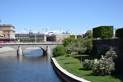 First view of Stockholm (lucasual) Tags: stockholm sky sun skyline architecture bridge river water trees garden lilac bank edge