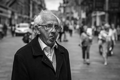 On The Tip Of His Tongue (Leanne Boulton) Tags: urban street candid portrait portraiture streetphotography candidstreetphotography candidportrait streetportrait streetlife closeup old elderly aged man male face facial expression look emotion feeling tongue mood atmosphere crooked glasses tone texture detail depthoffield bokeh naturallight outdoor light shade shadow city scene human life living humanity society culture people canon canon5d 5dmarkiii 70mm character ef2470mmf28liiusm black white blackwhite bw mono blackandwhite glasgow scotland uk monochrome