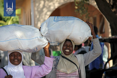 2 women take their Ramadan food parcel home from the Islamic Relief food distribution
