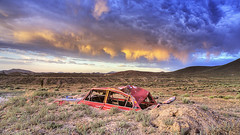 Crushing Weather (magnetic_red) Tags: car crushed junk rusted buried sky clouds storm stormy sunset mountains desert red pink sureal nevada