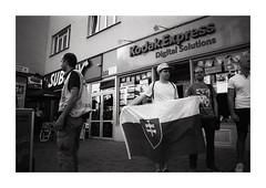 Man with flag (Thomas von Schlafenberg) Tags: nikon nikonf90x nikkor nikkor2828 nikkor28mm bratislava protest flag blackandwhite bw schwarzweiss streetphoto slovakia slovensko street people social epsonv500 foma fomapan fomapan200 universaldeveloper ishootfilm analog analogue film