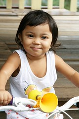 toddler on a tricycle (the foreign photographer - ฝรั่งถ่) Tags: toddler girl child tricycle yellow horn khlong thanon portraits bangkhen bangkok thailand canon kiss