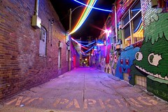 Haymarket, Lincoln NE (NDSUG0GR33N) Tags: lincoln nebraska ne capitol downtown haymarket district night city alley alleyway bright vibrant color colorful art urban environment light lights neon strip strips power line lines street no parking back pavement crack cracks detail details texture textures structure sony alpha a6000 rokinon 12mm f20 wide angle lens rainbow pink blue green yellow red reflection window old building buildings united states america electric electricity long exposure