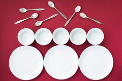 White plates, bowls and silver tea spoons on red background. Top view (Olga_Z1982) Tags: plate bowl tea spoon crockery cutlery silver red background white color geometric abstract modern contrast decoratedtable holiday topview round jewelery tableware row