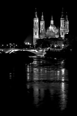 Night prayers (Daniel Nebreda Lucea) Tags: church iglesia pilar zaragoza europe europa religion payer oracion night noche city ciudad river rio reflection reflejos lights luces shadows sombras two dos architecture arquitectura black white blanco negro monochrome monocromatico noir composicion composition travel viajar building edificio construccion faith fe old antiguo basilica monumento monument water agua street calle bridge puente canon 60d 50mm cristianismo catolico
