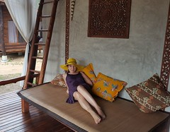 Relaxing in Thailand (! . Angela Lobefaro . !) Tags: thailand travel hat woman girl hut tropical pillow legs feet smile happy yellow purple mobile relax model 1person thailandia etnic ethnic ethnical bungalow pillows cuscini dress outfit veranda porch stair steps bench portico verandah patio