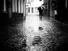 walking in the rain (Sandy...J) Tags: olympus atmosphere blackwhite monochrom street streetphotography city cobblestones rain walking urban noir white black