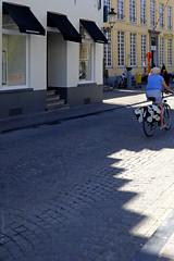 Et l'aventure (Join me on Facebook!) Tags: belgique belgium bruges brugge cycliste vélo bicycle bike bicyclette people street streetlife streetphoto streetphotography rue lady travel voyage dame oldlady oldpeople adventure journey trip pavés ombres magasin shop trottoir lumière bâtiments édifices cobblestones lightsshadows cobbledstreet