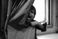 Shy game of Hide and Seek (Rahul Gaywala) Tags: curtain hide kid monochrome black white bw bnw whiteblack blackwhite passanger play seek shy stranger train window
