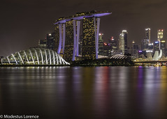 Busy city in the middle of a calm water. (Modestus Lorence) Tags: longexposure canon2470mmf28isii 1dxmarkii canon sands bay marina singapore water night landscape city