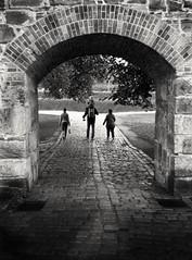 Beyond the gate (Bonsailara1) Tags: bonsailara1 oslo noruega norway blackandwhite blancoynegro gate puerta family familia paseo stroll field campo caminodepiedra stoneroad arch arco