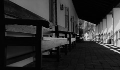 At the End of It (Rand Luv'n Life) Tags: odc our daily challenge san diego mission de alcala benches columns brick corridor shadow natural sun light cross monochrome blackandwhite short long