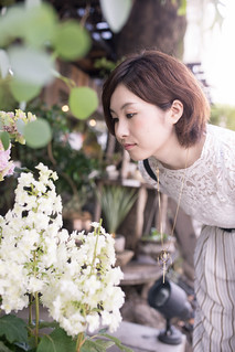 young woman looking at white hydrangea on street
