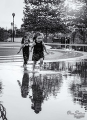 Sisters (JusDaFax) Tags: sisters girls toddlers playing water reflection running splashing drops trees sun bw blackwhite travel columbus ohio