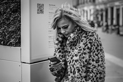 Call of Nature (Leanne Boulton) Tags: urban street candid portrait portraiture streetphotography candidstreetphotography candidportrait streetportrait streetlife closeup woman female girl face facial expression look emotion feeling mobile phone fur coat furry animal beautiful blonde makeup eyelashes technology tone texture detail depthoffield bokeh naturallight outdoor light shade shadow city scene human life living humanity society culture fashion canon canon5d 5dmkiii 70mm character ef2470mmf28liiusm black white blackwhite bw mono monochrome blackandwhite glasgow scotland uk