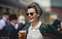 A Smile And A Pint (Andy Darby) Tags: candid severnvalleyrailway 1940s bridgnorth railway pint drinking woman glasses sunglasses green smile red lipstick street streetphotography streetview