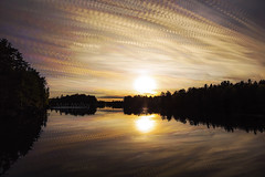 Sunset Cloud Painting (Matt Molloy) Tags: mattmolloy timelapse photography timestack photostack movement motion orange yellow sun colourful sky sunset clouds trails lines trees calm water reflection lake mortonbay morton ontario canada landscape nature lovelife