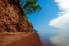 coastlines (Port View) Tags: fujixe2 blomidon novascotia canada cans2s 2017 summer millecreek minasbasin cliff cliffs trees leaning water calm shore blue sky white clouds capeblomidon tide tidal