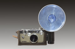 A 1958-1966 Argus C-3 match-matic 35mm camera with a blue Sylvania flash bulb and reflector-The design of the camera is attributed to Gustave Fassin. (thstrand) Tags: 1950s 1960s 20thcentury american argusc3 artifact artifacts blueflashbulb brand brands camera cameras film flashattachment flashbulbs flashgun gears gustavefassin historic history industrialdesign industry isolated knobs leathercase lens manual matchmatic nobody old photo photography rangefinder reflector reflectors snapshot snapshots studioshot sylvania usa unitedstatesofamerica vintage twotonetan