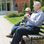 Senior living community - 2 seniors sitting on a bench outdoors thumbnail