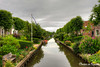 Dutch Canal of IJlst (Charlene van Koesveld) Tags: ijlst friesland frieseelfsteden fries elfstedentocht overtuinen lindebomen bomen groen water gracht canal cloudscape clouds summer wolken zomer river green flowers trees garden city cityscape town architecture landscape reflection house holland dutch netherlands nederland boats boten bridge flag