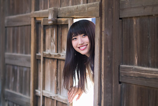 Young woman entering old Japanese house gate
