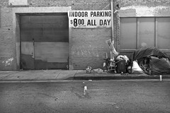 Perry Street, South of Market - San Francisco, CA (Rex Mandel) Tags: street streetpeople sanfrancisco sf homeless homelesscamp brickwall bricks garage rollupdoor boardedupwindows parkinggarage sign eyecontact candid staring blackandwhite bw cigarette smoking sidewalk