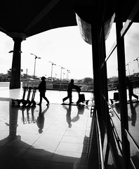Coming And Going (kieronjameslong) Tags: bnw bw blackandwhite shadow refelction silhouette arrival departure airport tourists tourism travel man woman backlit backlight street streetphotography