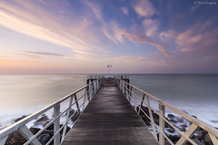 First Lights Over The Walkway. (dasanes77) Tags: canoneos6d canonef1635mmf4lisusm tripod landscape seascape cloudscape waterscape longexposure dawn sunrise clouds pink orange blue horizon walkway wood rocks waves castellon xilxes