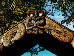 The Marae Entrance (Steve Taylor (Photography)) Tags: gate entrance ferryroad marae heads fish face hands art carving blue brown black green wooden wood leaves tree maori ferryrd