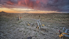 Driven Down (magnetic_red) Tags: bike buried motorcycle dirt handlebars sunset clouds outdoors landscape summer storm stormy mountains sky warm pink red nevada internationalcarforest goldfield