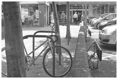 In The Shade (h_cowell) Tags: street streetphotography film filmisnotdead filmphotography believeinfilm blackandwhite monochrome hp5 praktica sun sunny shade grain grainy bicycle timeless faded analogue macclesfield
