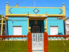 Vivenda Justo (cyclingshepherd) Tags: 2017 julho july europe europa portugal algarve olhao olhão vivenda casa house justo street tiled tiling gate wall colourful colorful 1942 green red blue yellow frontage sky architecture building geometric aluminium aluminum 26 porch gates net netting saint santo shutter shutters handle handles steps triangles door doors color colour colors colours cor cores cottage gatepost gateposts cute