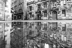 Die Frau an der Ecke - the woman at the corner (ralfkai41) Tags: schottland strasse street wasser bw reflexion blackwhite mirroring schwarzweis water sw city streetfotografie einfarbig edinburgh monochrom spiegelung pudlegram