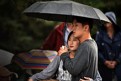 Love Under the Umbrella (Poocher7) Tags: portrait people umbrella raining raindrops trees umbrellas romantic love couple together asiancouple lovely beautiful wonderful affectionate caress hug holdingeachother tenderness prettygirl handsomeguy redlips prtection protection touching candid streetphotography sweet waterloo ontario canada