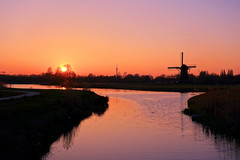Weather and sunset scenery, dutch style (STEHOUWER AND RECIO) Tags: weather weer sunset zonsondergang dutch scenery landscape view colours windmill molen light late water reflections rotterdam netherlands nederland holland pendrecht pendrechtsemolen spring reed grass tower green path swan swans silhouettes trees sky lucht sony dscrx100 evening avond