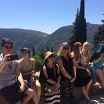 Honors students take a break and sit on a stone ledge overlooking Delphi.