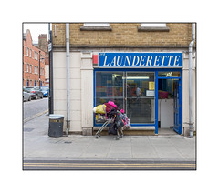 Eccentric Women's Launderette Visit, East London, England. (Joseph O'Malley64) Tags: eccentric eccentricity character laundry launderette laundromat shop shopfront cornershop eastlondon eastend london england uk britain british greatbritain artdecobuilding pillars mouldings stucco stuccowork stonework renovated remedialwork brickwork bricksmortar cement repointing pointing drainpipes steelsecuritymesh door doorway entrance exit signs signage lamppost stopcock accesscovers burglaralarm parkedcars cobbles cobblestones cobbledroadsurface pavement granitekerbing tactilepavingforthevisuallyimpaired tarmac doubleyellowlines noparkingatanytime parkingrestrictions shoppingtrolley personalpossessions bags clothing collectiontin mentalhealth refusebin litterbin fujix x100t accuracyprecision