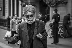 Raising A Hand (Leanne Boulton) Tags: monochrome people portrait urban street candid portraiture streetphotography candidstreetphotography candidportrait streetportrait streetlife eyecontact candideyecontact old elderly man male sikh face facial expression look emotion feeling turban style stylish hand gesture tone texture detail depthoffield bokeh naturallight outdoor light shade shadow city scene human life living humanity society culture canon canon5d 5dmkiii 70mm character ef2470mmf28liiusm black white blackwhite bw mono blackandwhite glasgow scotland uk