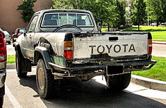Toyota With Interesting Bodywork (Eyellgeteven) Tags: toyota yota truck pickup pickuptruck 4x4 fourwheeldrive minitruck compact compactpickup 1980s beater beatup dilapidated rustyandcrusty rundown toy rust rusty rusted dented dents dent bodywork primer paint patch patched silver gray japanese madeinjapan import jalopy junker junk survivor old oxidized oxidation dailydriver classic vintage vehicle eyellgeteven decay eyesore ugly weathered welded worktruck farmtruck