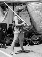Wielding Her Sword (John Kocijanski) Tags: sword woman fencing people blackandwhite streetphotography streetcandid streetfair canon24105mmf4l canon5dmkii
