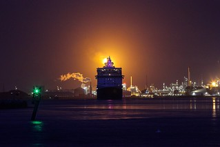 Cruiseship Queen Elisabeth in front of the fire at Shell Rotterdam-Pernis