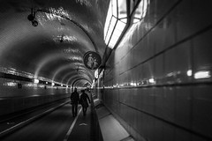to be a part of a pair / deep tunnel, long lines (Özgür Gürgey) Tags: 2017 35mm bw d750 darkcity hamburg nikon samyang architecture depth grainy leading lines lowlight people sign vignette