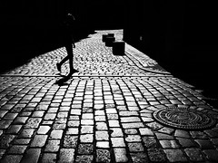 spotlight (Sandy...J) Tags: atmosphere alone blackwhite bw city cobblestones darkness photography light silhouette monochrom man street streetphotography urban noir backlight walking olympus