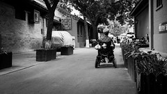 Equal (Go-tea 郭天) Tags: pékin beijingshi chine cn beijing hutong gulou old ancient tradition traditional historic history historical building construction houses narrow alley transportation handy handicap wheel chair electric bags wowan grandma granny movement moving through passenger power alone lonely sad equal equality trees equipment back backside candid street urban city outside outdoor people bw bnw black white blackwhite blackandwhite monochrome naturallight natural light asia asian china chinese canon eos 100d 24mm prime poor sadness slow