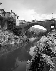 Kanal ob Soči, Slovenia. (wojszyca) Tags: wanderlust cameras travelwide 90 4x5 largeformat schneider kreuznach angulon 90mm ilford fp4 hc110 gossen lunaprosbc epson v800 kanal slovenia bridge river rain rock town