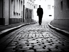 The sound of silence (Sandy...J) Tags: street streetphotography monochrom man blackwhite atmosphere alone silhouette urban noir walking cobblestones city black white