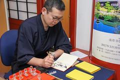 Monk inscribes a vistor's Goshuin notebook, Senso-ji Temple (Sharaz Jek) Tags: asakusa goshuinnotebook honorableredstampnotebook tokyo japan travel travelphotography buddhism buddhistmonk sensojitemple calligraphy japaneseculture canoneos550d